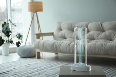UV sterilizer lamp on table at home. Space for text Stock Photo
