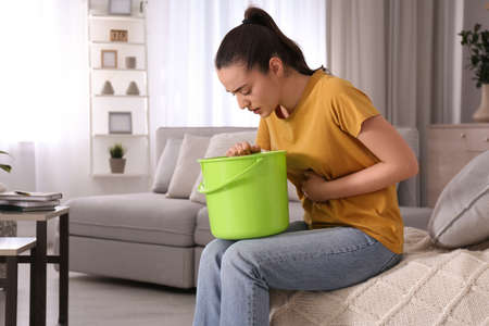 Young woman with bucket suffering from nausea at home, space for text. Food poisoning Stockfoto