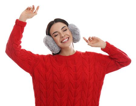 Beautiful young woman wearing earmuffs on white background