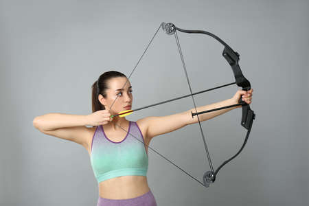 Young woman practicing archery on light gray background