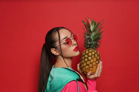Young woman with fresh pineapple on red background. Exotic fruit Archivio Fotografico