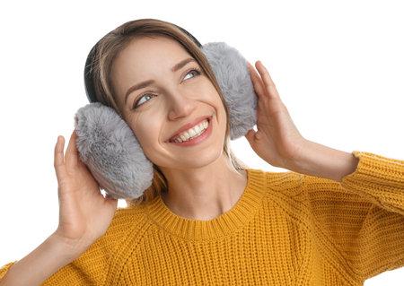 Happy woman wearing warm earmuffs on white background