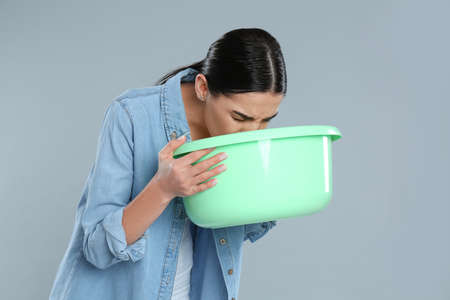 Woman with basin suffering from nausea on grey background. Food poisoning
