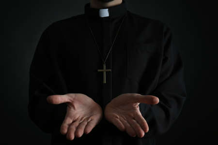 Priest reaching out his hands on dark background, closeup