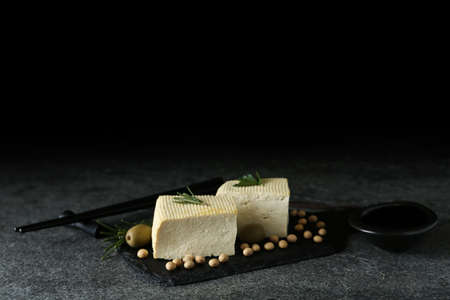 Pieces of delicious tofu with herbs, olives and soy on grey table, space for text