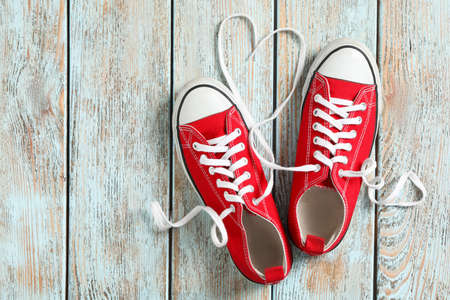 Pair of stylish shoes with laces on wooden background, flat lay. Space for text