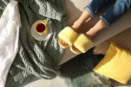 Woman with cup of tea wearing soft comfortable slippers at home, top view