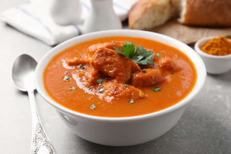 Bowl of delicious chicken curry on light grey table