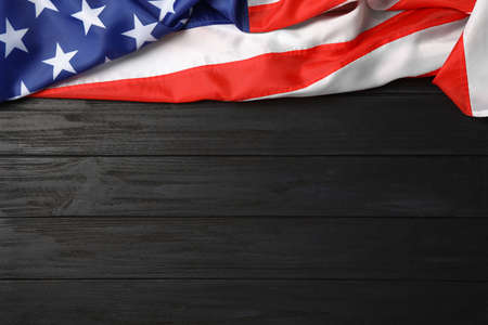 American flag on black wooden table, top view with space for text. Memorial Day