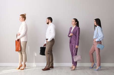 Businesspeople waiting in queue near light wall indoors