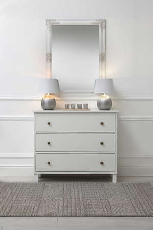 White chest of drawers with lamps near mirror in room. Interior design