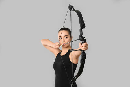 Young woman practicing archery on light grey background
