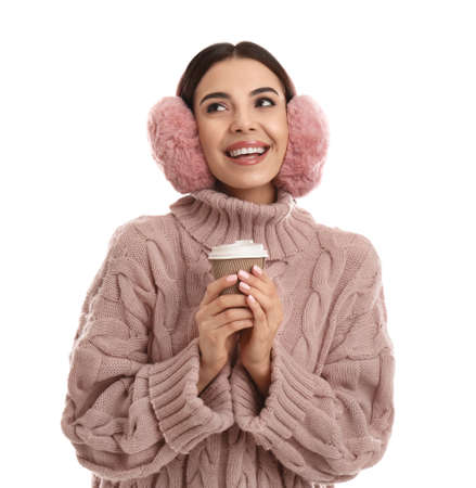 Beautiful young woman in earmuffs with cup of drink on white background