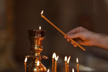 Man lighting candle near stand in church, closeup. Baptism ceremony Standard-Bild