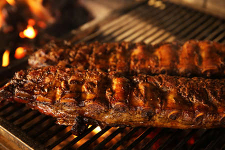 Grilling grate with tasty pork ribs in oven, closeup