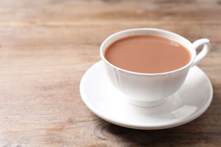 Delicious tea with milk in white cup on wooden table