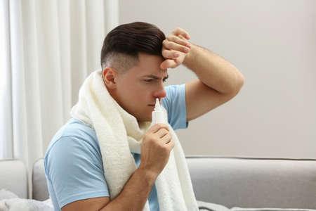Ill man using nasal spray at home