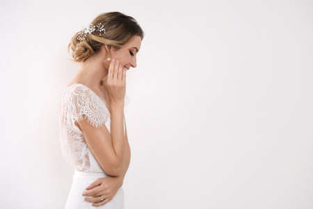 Young bride with elegant wedding hairstyle on light background. Space for text