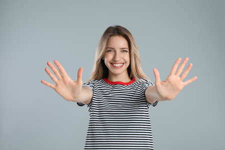 Woman showing number ten with her hands on light grey background