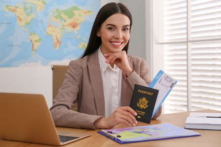 Travel agent with ticket and passport at table in office