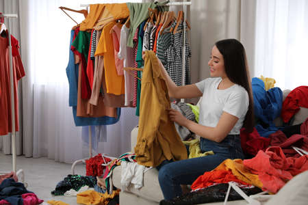 Happy young woman with lots of clothes on sofa in room. Fast fashion Stock fotó