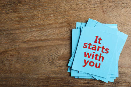 Roles and responsibilities concept. Blue paper cards with phrase It stars with you and space for text on wooden table, top view Banque d'images
