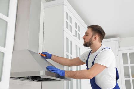 Worker repairing modern cooker hood in kitchen