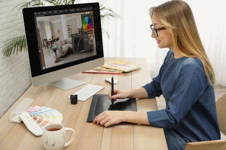 Professional retoucher working on graphic tablet at desk Banco de Imagens