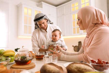快乐的穆斯林家庭和小儿子在厨房的餐桌上