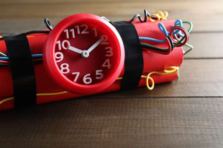 Dynamite time bomb on wooden table, closeup