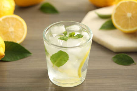 Cool freshly made lemonade in glass on wooden table, closeup
