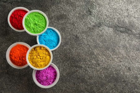 Colorful powder dyes on grey background, flat lay with space for text. Holi festival
