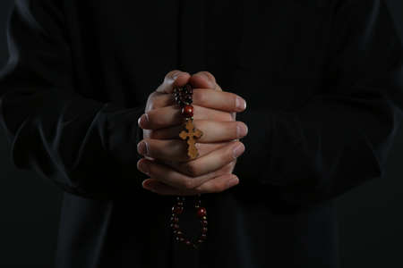 Priest with rosary beads praying on black background, closeup