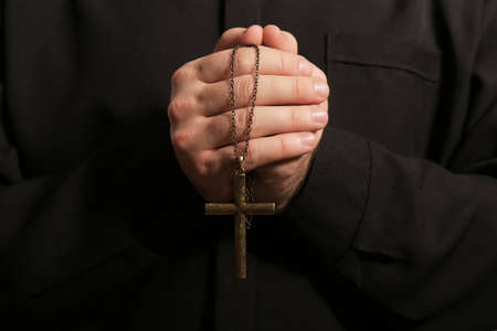 Priest in cassock with cross, closeup view