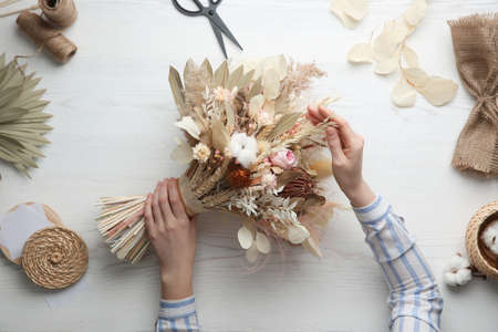 Florist making beautiful bouquet of dried flowers at white table, top view