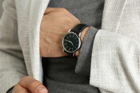 Businessman in jacket with luxury wrist watch, closeup