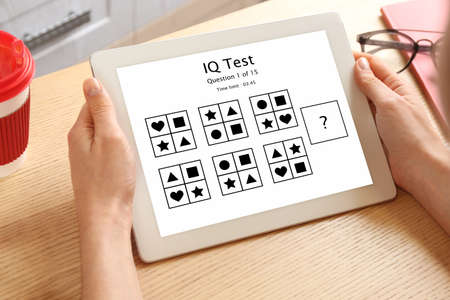 Woman using tablet for taking IQ test indoors, closeup