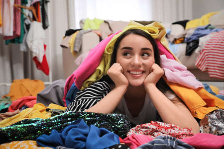 Happy young woman with lots of clothes on floor in room. Fast fashion