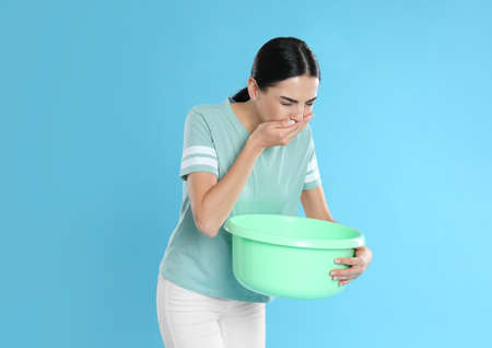 Woman with basin suffering from nausea on light blue background. Food poisoning