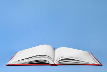 Open book with red cover on light blue background. Space for text