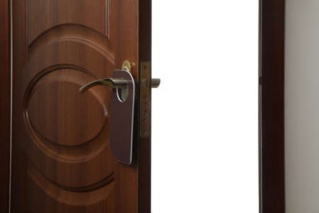 Hotel wooden door with blank hanger on white background, closeup