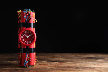 Dynamite time bomb on wooden table against black background. Space for text Imagens