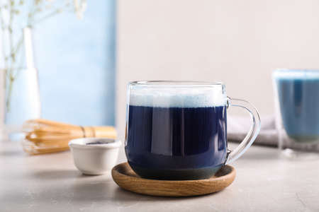 Delicious blue matcha drink on light grey table