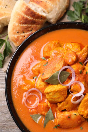 Delicious chicken curry in pan on wooden table, flat lay Reklamní fotografie