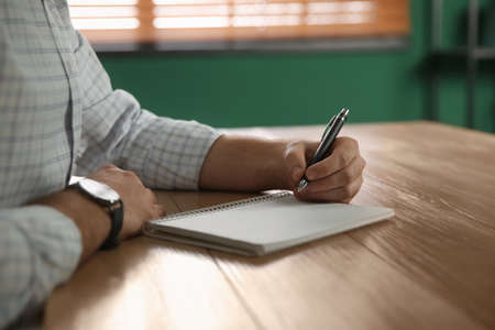 Left-handed man writing in notebook at wooden table indoors, closeup