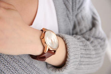 Woman with luxury wristwatch on blurred background, closeup