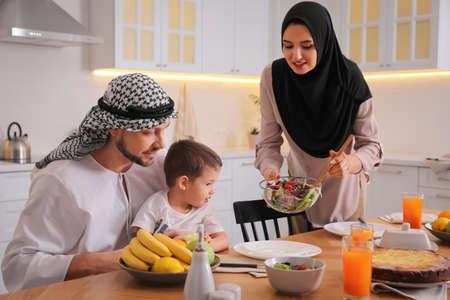 一起吃在厨房里的愉快的穆斯林家庭