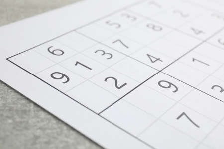 Sudoku puzzle on grey table, closeup view