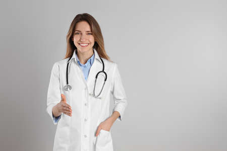 Happy female doctor offering handshake on light grey background. Space for text Banque d'images