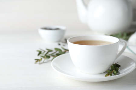Cup of green tea and eucalyptus leaves on white table. Space for text